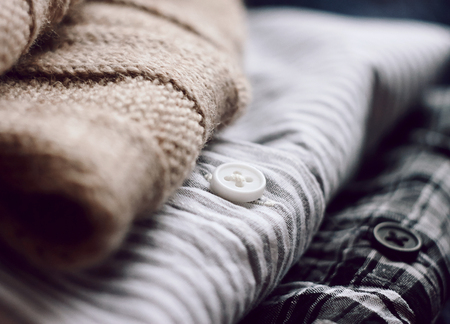 A neat stack of clothes - a beige scarf and two shirts. One plaid shirt, the other striped.