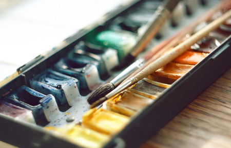 Box with watercolor in cuvettes and brushes lie on a wooden surface, illuminated by the gentle sun Foto de archivo