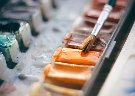 Watercolor paint in cuvettes of different colors-blue, orange and others and a brush for drawing with a large thick pile