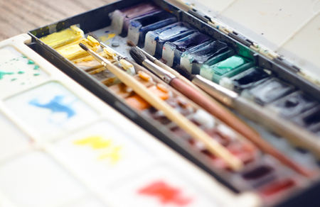 Watercolor paints in cuvettes are in a folding box of metal and plastic, along with a set of brushes from squirrel hair and pony hair