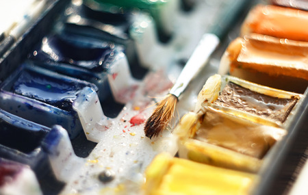The brush for drawing lies among cuvettes with watercolor paint of different colors: turquoise, blue, orange, yellow, beige and others.