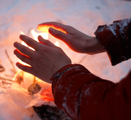 Man warms bare frozen hands over an improvised small fire, divorced in the middle of the snow in winter