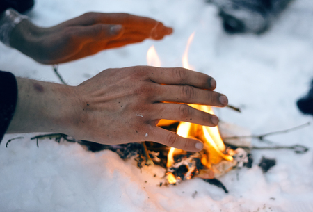 Man warms frozen hands over a fire, divorced in the snow Banco de Imagens