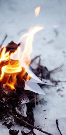 A small fire in the forest in the winter, which burn twigs and paper for ignition