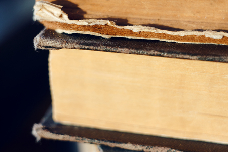 Several old multi-page books, yellowed by time, lie in a stack