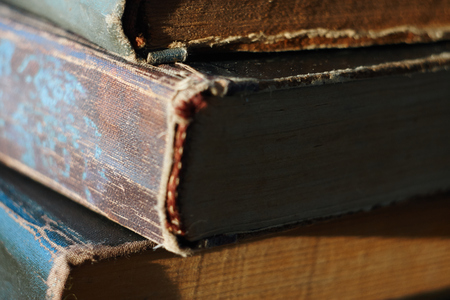 A few old vintage books, with yellowed pages and cracked spines, are stacked on top of each other