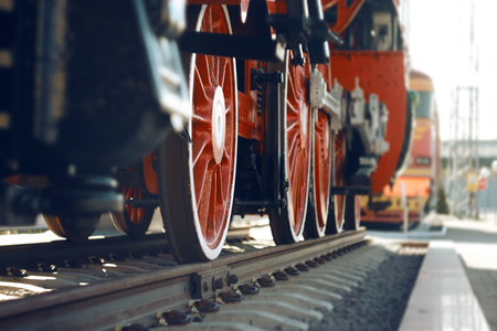 The wheels of the old heavy locomotive, painted red and standing on the rails, which are in the Museum