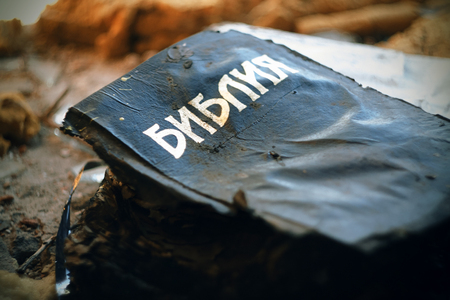 In an abandoned place lies a burned Bible, in a black cover, which someone once burned. Even with the fire, the book survived