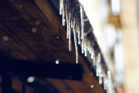 Icicles shining in the sun, hanging from the roof and melting, because the thaw began.