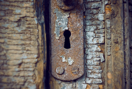 Old rusty keyhole in the old wooden door, which is in very poor condition and which has not been opened for a long time