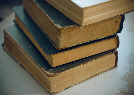 Stack vintage shabby time of encyclopedias that contains many knowledge in the dark cover is on the table