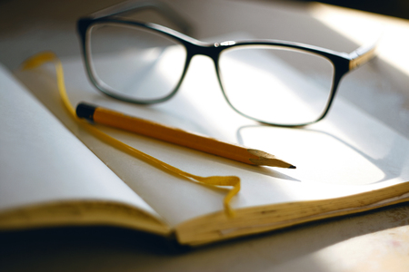On the table lay open Notepad with yellow tape and empty pages, yellow sharpened pencil and black-rimmed glasses, illuminated the bright sunlight Фото со стока