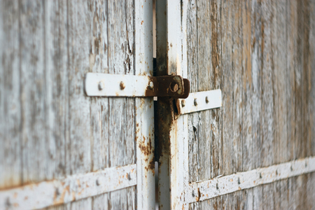 Old wooden gate with rusty latch and painted white. White paint flakes with time.