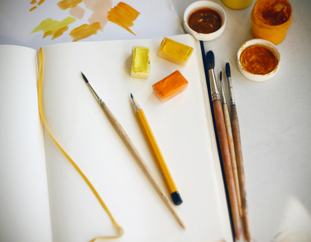 On a light table are art supplies: paints, pencil, brushes, paper palette and an empty notebook for drawing. Everything is prepared to create an illustration in yellow-orange colors. Stock fotó