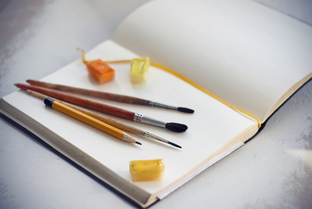 On an open notebook with blank pages and yellow tape are brushes of squirrel hair, yellow pencil and watercolors in cuvettes of yellow and orange shades.