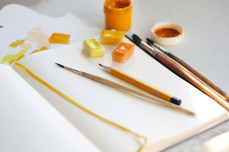 Different art supplies of yellow and orange colors lie on the white surface of the table.