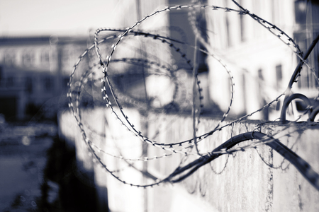 Black and white conceptual image of a sharp barbed wire, coiled on a fence that encloses the prison.