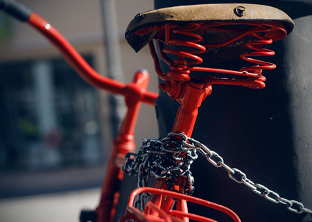 Beautiful bright vintage red bike with old leather saddle. The bike is attached to a pole on a metal chain.