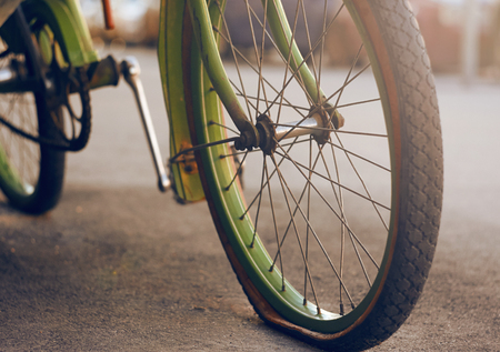 Beautiful retro bike green, standing on the asphalt with a flat tire on the wheel and illuminated by the sun