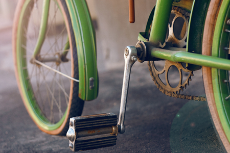 Rusty abandoned green retro bike, standing on an asphalt street on a Sunny day