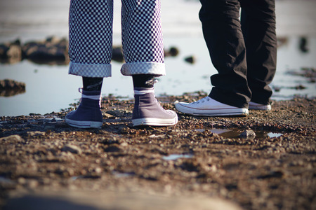 Two people in pants and sneakers are on the rocky beach in Sunny weather
