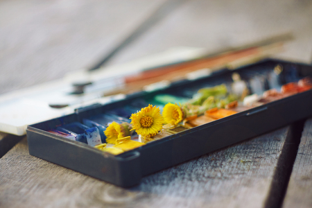 On the wooden table is an old vintage palette with cuvettes, a set of brushes and a few blossoming flowers coltsfoot Foto de archivo