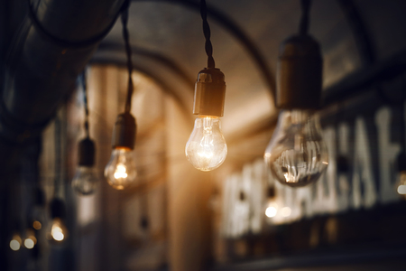 Glass light bulbs hanging on the wires on the roof near the cafe, glow brightly in the darkness of the night