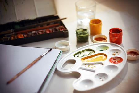 On the table there are watercolor paints in a vintage box, a large notebook for drawing on a spring, a glass of water for washing brushes, open gouache paints in jars and brushes. Фото со стока