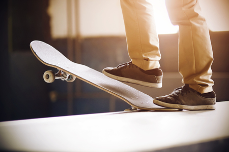 A guy in beige pants and black sneakers stands on a ramp on a skateboard and does a Drop In trick, illuminated by the joyful sunlight