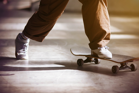 A guy in beige loose pants and white running shoes pushes off the floor and rides a skateboard, illuminated by the lighting of different colors.