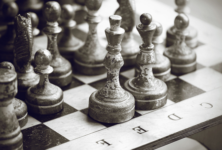 Black and white image of silvery shabby old large chess pieces standing on the chessboard.