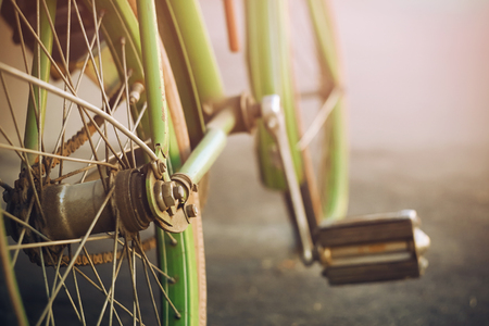 Green retro bike, rusted with time, stands on the asphalt lit by pleasant sunlight.