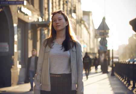 A beautiful red-haired girl with inspiration on her face walks along the sunlit street of the city in the evening.