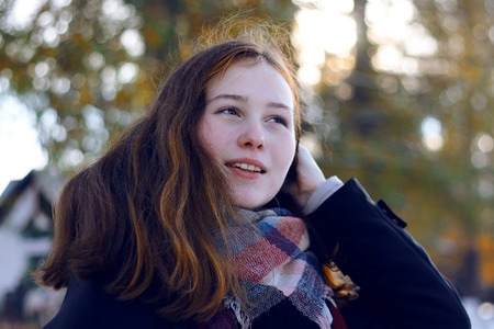 A beautiful girl with reddish hair smiles and removes a long strand of hair over her shoulder, being in the Park in the cold season