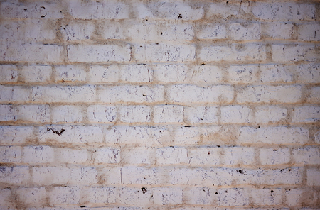 Abstract solid background depicting an old white wall, painted, worn and scratched by time.