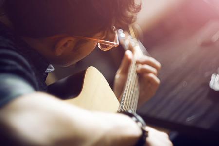 A curly-haired inspired guy in a shirt and pink glasses plays a melody on an acoustic guitar, illuminated by pink sunlight.