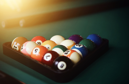 Multi-colored balls for the game of Billiards are folded in a triangle and prepared for the game, and next are two cue. Фото со стока