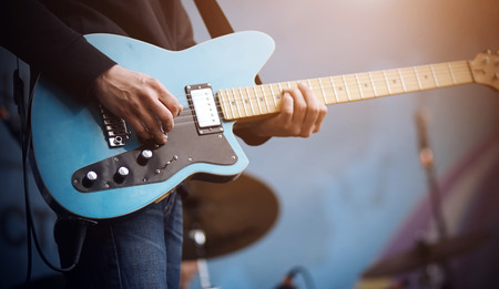 The guitarist performs a melody on a blue electric guitar, which is connected by a wire to the equipment, on a blue background.