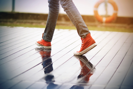 A man in red sneakers walking on a wet boardwalk, on the fence of which hangs a lifeline, in the rain.