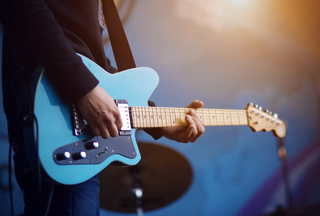 A man in a black sweater in blue jeans plays a blue electric guitar, illuminated by sunlight, on a blue background.