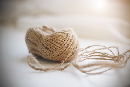 A coil of beige coarse hemp rope lying on a white background and illuminated by sunlight. Фото со стока