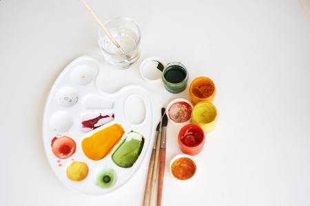 On a white background are art supplies: gouache paints of yellow, red and green colors, a plastic palette, brushes of squirrel fur and a glass with water for washing brushes. Фото со стока
