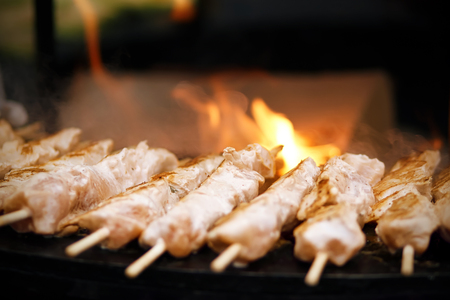 Small delicious kebabs on wooden skewers are fried on an open fire on a summer day