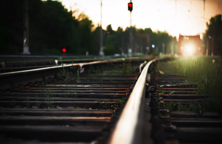 Bright light from the headlights of the approaching train, which rides on rails with wooden sleepers in the countryside. Next to the railway tracks are red traffic lights, warning of danger.