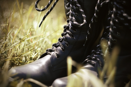 Black rough leather army high boots with black and white laces standing in the grass, illuminated by sunlight.