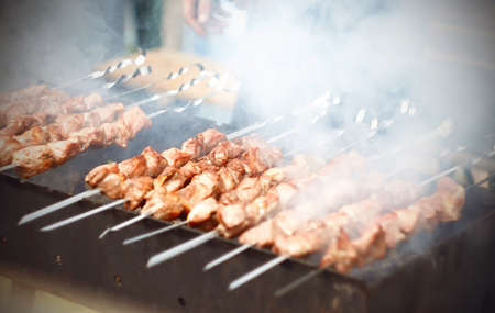 Delicious kebabs skewered on metal skewers and cooked on the grill in the summer outdoors