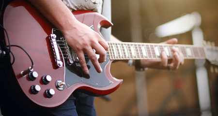 A man plays a melody on a red gothic six-string electric guitar on stage at a concert