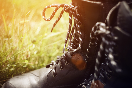 Black leather military rough boots with a high top and black and white laces tied in a bow, illuminated by bright orange sunlight and stand in the grass in the summer. Фото со стока