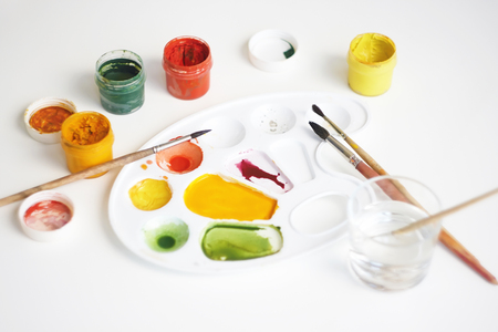 On a white background there is a still life with art supplies: gouache paints of different colors, brushes, palette and a glass of water to dilute the paint.