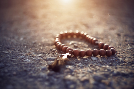 Wooden Catholic rosary with a cross lie on a rocky surface, illuminated by sunlight, as an inspiration from above